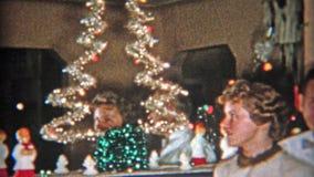 DETROIT, MICHIGAN 1953 : Maman et fille devant le grand arbre de Noël banque de vidéos