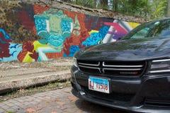DETROIT, MICHIGAN, VEREINIGTE STAATEN - 22. Mai 2018: Schwarzes Dodge-Ladegerät vor einer Wand mit Graffiti herein in die Stadt stockfotografie