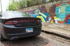 DETROIT, MICHIGAN, VEREINIGTE STAATEN - 22. Mai 2018: Schwarzes Dodge-Ladegerät vor einer Wand mit Graffiti herein in die Stadt stockbilder