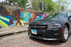 DETROIT, MICHIGAN, VEREINIGTE STAATEN - 22. Mai 2018: Schwarzes Dodge-Ladegerät vor einer Wand mit Graffiti herein in die Stadt stockfotos