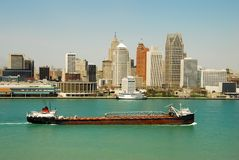Detroit skyline by day. Barge going up the Huron River in front of Detroit skyline royalty free stock images