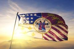 Detroit-Stadt des Flaggentextilstoffgewebes Vereinigter Staaten, das auf den Spitzensonnenaufgangnebelnebel wellenartig bewegt stockfotografie