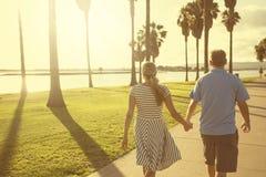 Detrás de vista de un centro envejeció los pares que caminaban juntas llevando a cabo las manos Fotografía de archivo