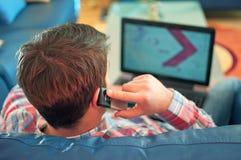 Detrás del individuo joven que usa la computadora portátil y el teléfono Fotos de archivo