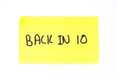 Detrás en 10 escritos en una nota pegajosa Fotografía de archivo