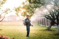 dettagli agricoli - funzionamento dell'agricoltore, antiparassitari di spruzzatura nel frutteto di frutta Fotografia Stock Libera da Diritti