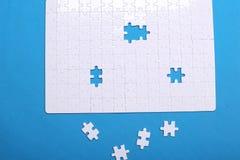 Dettagli bianchi di un puzzle su un fondo blu Un puzzle è un'unità di elaborazione Immagini Stock Libere da Diritti