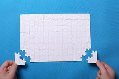 Dettagli bianchi di un puzzle su un fondo blu Un puzzle è un'unità di elaborazione Fotografie Stock