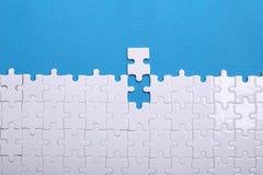 Dettagli bianchi di un puzzle su un fondo blu Un puzzle è un'unità di elaborazione Immagine Stock Libera da Diritti