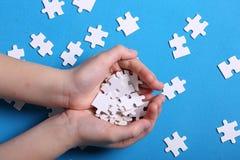 Dettagli bianchi di un puzzle su un fondo blu Un puzzle è un'unità di elaborazione Fotografie Stock Libere da Diritti