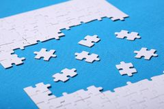 Dettagli bianchi di un puzzle su un fondo blu Un puzzle è un'unità di elaborazione Immagini Stock
