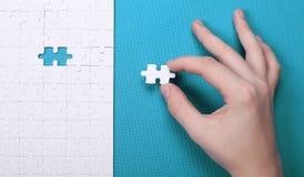 Dettagli bianchi di un puzzle su fondo verde Un puzzle è un puz Fotografia Stock Libera da Diritti