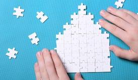 Dettagli bianchi di un puzzle su fondo verde Un puzzle è un puz Fotografia Stock