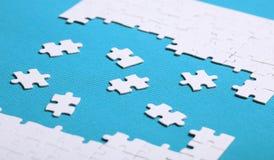 Dettagli bianchi di un puzzle su fondo verde Un puzzle è un puz Fotografie Stock