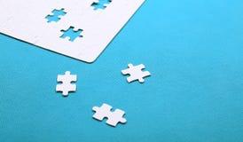 Dettagli bianchi di un puzzle su fondo verde Un puzzle è un puz Fotografie Stock Libere da Diritti
