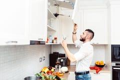 Dettagli del cuoco unico che cucinano nella nuova cucina moderna, alcool di versamento in vetro Immagine Stock