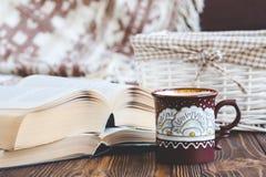 Dettagli della natura morta nel salone dell'interno della casa Bella tazza di tè, legno tagliato, libri e cuscini, candela su bac immagine stock libera da diritti