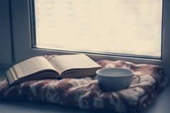 Dettagli della natura morta nell'interno della casa Maglione, tazza, lana, accogliente, libro, candela moody Concetto accogliente immagini stock libere da diritti