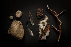 Dettagli della natura - pietre, piume, corteccia di albero e ramo sul nero Immagine Stock