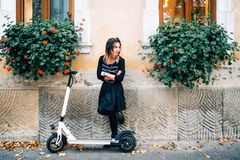Dettagli di stile di vita, ragazza felice con i fiori in città urbana che gode del motorino elettrico Felicità e concetto spensie fotografia stock libera da diritti