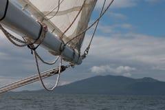 Dettagli di una barca a vela, di una vela bianca, di un boma e degli strati prima che il fondo confuso del mare e la montagna abb immagini stock libere da diritti