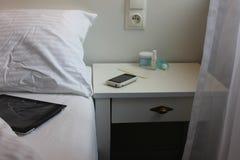 Dettagli di vista della camera da letto con il letto, tavola laterale con lo smartphone e cosmetici su  Fotografia Stock