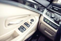 Dettagli interni di cuoio dell'automobile della maniglia di porta con i comandi e gli adeguamenti delle finestre Fotografia Stock
