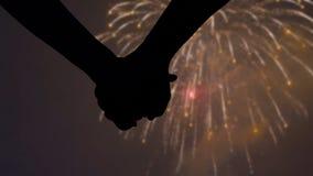 Dettagli le siluette delle mani che si uniscono durante la celebrazione dei fuochi d'artificio di notte stock footage
