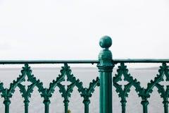 Dettagli verdi del recinto del ferro con il mare nei precedenti Fotografia Stock