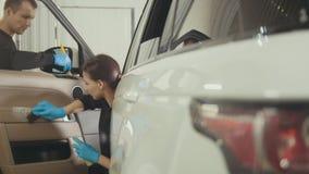 Dettagliare dell'automobile - la donna sta pulendo il cruscotto in veicolo di lusso immagini stock libere da diritti