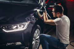 Dettagliare dell'automobile - uomo con il lucidatore orbitale nell'officina riparazioni automatica Fuoco selettivo immagini stock libere da diritti