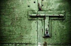 Dettaglio alto di fine arrugginita della porta di colore verde con il lucchetto ed il bullone Immagini Stock