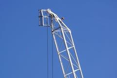 Dettaglio bianco alto della gru a torre contro cielo blu luminoso Immagini Stock