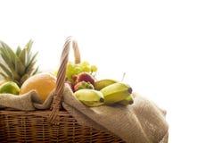 Dettaglio dal lato su un canestro in pieno di bio- frutta fresca su fondo bianco Immagini Stock