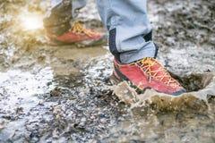 Dettaglio degli stivali di trekking in un fango Stivali e spruzzata d'escursione fangosi di acqua Equipaggi la spruzzatura in fan Fotografia Stock Libera da Diritti