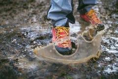 Dettaglio degli stivali di trekking in un fango Stivali e spruzzata d'escursione fangosi di acqua Equipaggi la spruzzatura in fan Immagine Stock