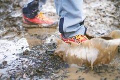 Dettaglio degli stivali di trekking in un fango Stivali e spruzzata d'escursione fangosi di acqua Equipaggi la spruzzatura in fan Fotografie Stock