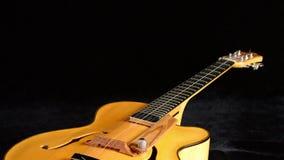 Dettaglio dei cerchi, della corda, del corpo, della bocca e del ponte della chitarra spagnola classica tipica che gira nel fondo  video d archivio