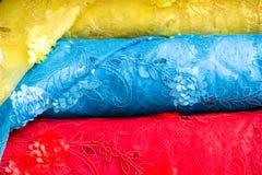 Dettaglio dei rotoli del tessuto impilati nei colori gialli, blu e rossi da vendere ad un deposito del tessuto immagine stock libera da diritti