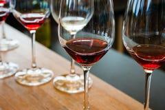 Dettaglio dei vetri di vino con vino rosso sul contatore di legno Fotografie Stock