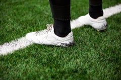 Dettaglio del calciatore di calcio sulla linea bianca sul campo di football americano di calcio con erba artificiale Immagini Stock Libere da Diritti