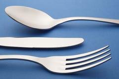 Dettaglio del cucchiaio del coltello della forcella sopra un fondo strutturato blu cutlery Fotografia Stock