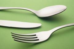 Dettaglio del cucchiaio del coltello della forcella sopra un fondo verde cutlery Fotografia Stock