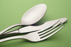 Dettaglio del cucchiaio del coltello della forcella sopra un fondo verde cutlery Immagini Stock