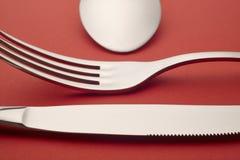 Dettaglio del cucchiaio della forcella del coltello sopra un fondo rosso cutlery Fotografia Stock Libera da Diritti
