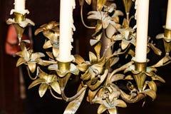 Dettaglio del primo piano di vecchio candeliere bronzeo con le candele che gocciolano cera fotografie stock