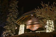 Dettaglio del segno della casetta di Kandahar con le luci di Natale alberi affollati fotografia stock