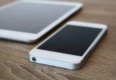 Dettaglio del telefono cellulare bianco e della compressa bianca Fotografie Stock