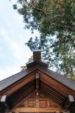 Dettaglio del tetto di legno della struttura del santuario Hokkaido Jingu dell'Hokkaido con gli alberi e del cielo nel fondo nell Fotografia Stock