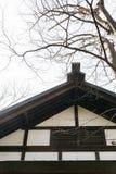 Dettaglio del tetto di legno della struttura del santuario Hokkaido Jingu dell'Hokkaido con gli alberi e del cielo nel fondo nell Immagine Stock
